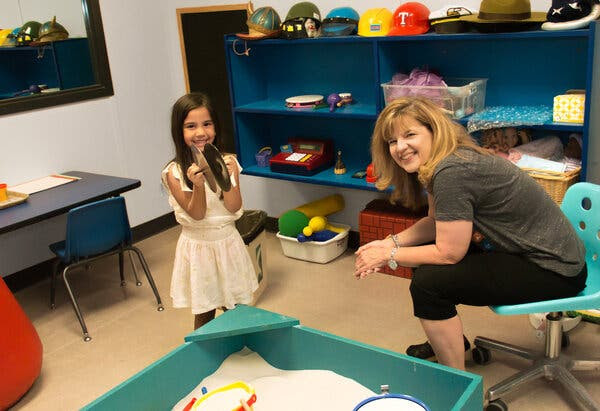 Dee Ray poses with a young girl (not a patient) in a play room at her Texas offices. Many kids who can't express their emotions in words can do it easily through play.