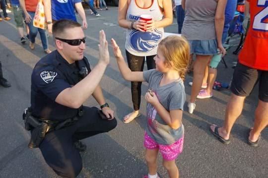Policeman giving little girl high five