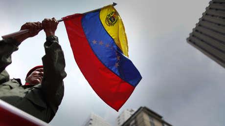 Un trabajador venezolano ondea la bandera de su país en Caracas, en mayo de 2012.