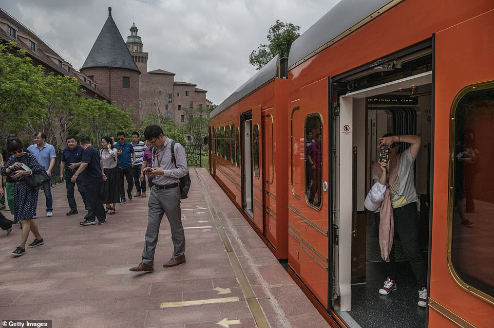 Employees and visitors disembark from a train after arriving at the Ox Horn campus