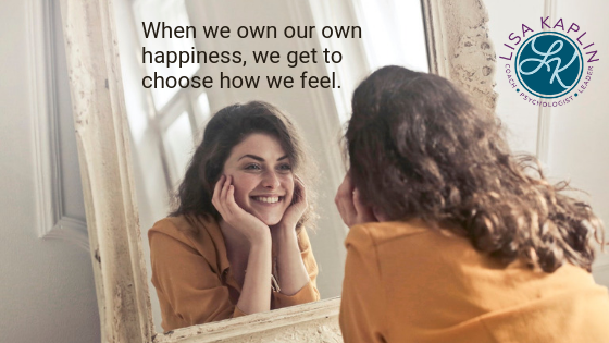 "A photo of a young white woman staring into a mirror. We see her reflection and she is smiling. Above her reflection is the text ""When we own our own happiness, we get to choose how we feel."" The Lisa Kaplin logo is in the top right corner."