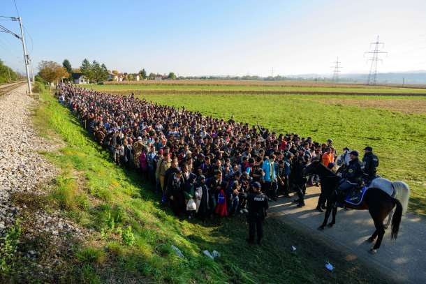 -- AFP PICTURES OF THE YEAR 2015 -- Police escort migrants and asylum seekers as they walk to a refugee centre after crossing the Croatian-Slovenian border near Rigonce on October 24, 2015. Bulgaria, Romania and Serbia threatened to close their borders if EU countries stopped accepting migrants, as European leaders prepared for a mini summit on the continent's worst refugee crisis since World War II. AFP PHOTO / JURE MAKOVEC
