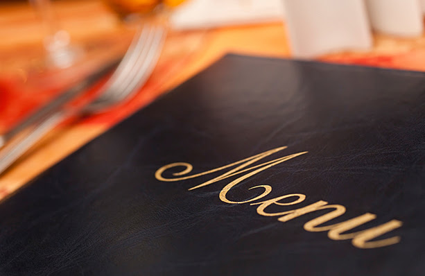 The front cover of a food menu with silverware in the background.