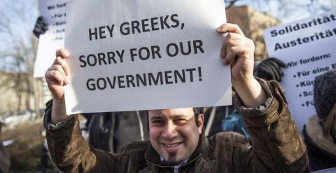 """""""Hey griegos, perdón por nuestro Gobierno"""". Un manifestante sujeta un cartel durante una protesta frente al Ministerio de Finanzas alemán. - EFE"""