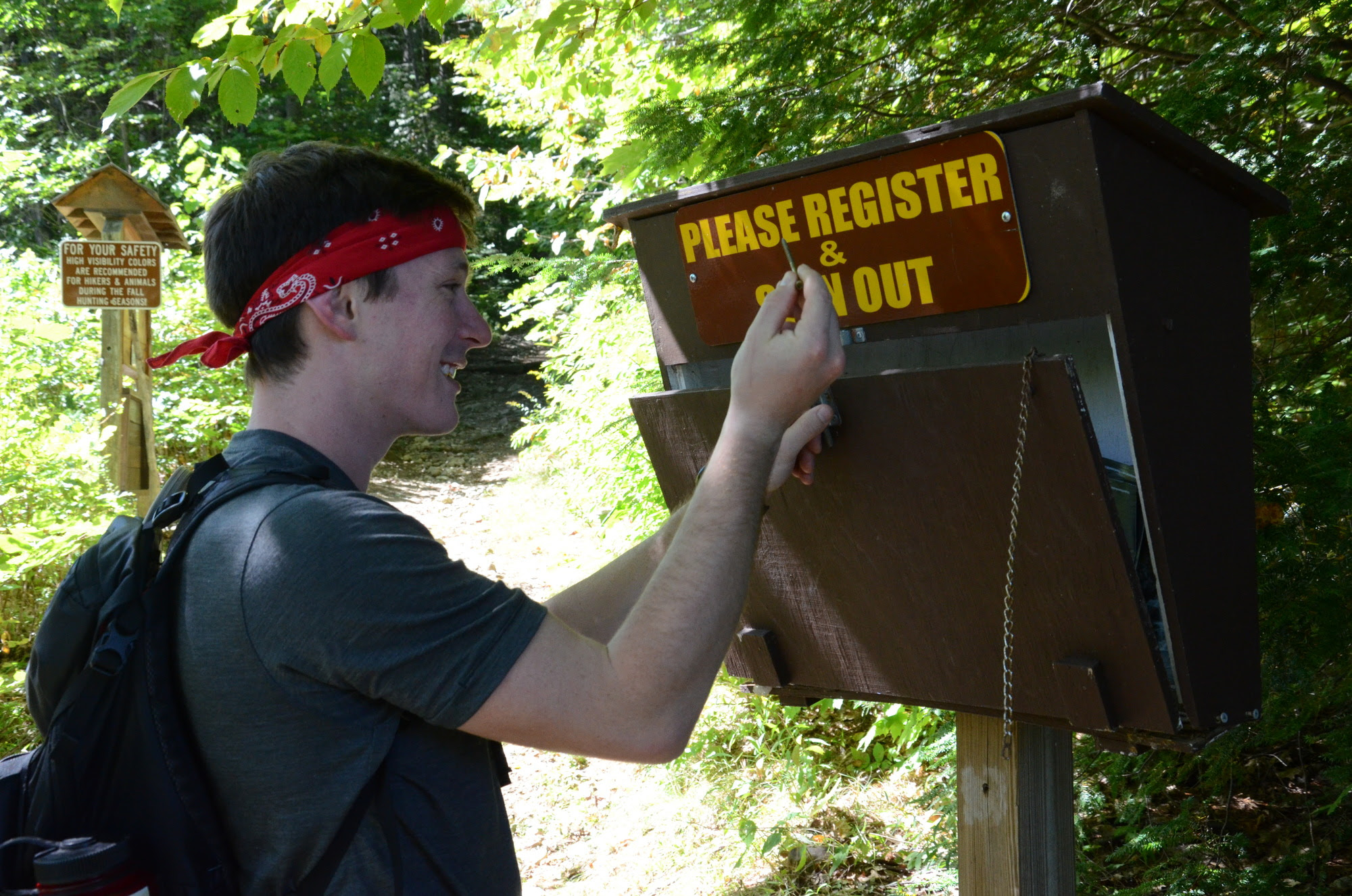 Hiker signing in at trail register