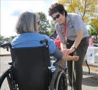 Medical Reserve Corps volunteer talking to person in a wheelchair.