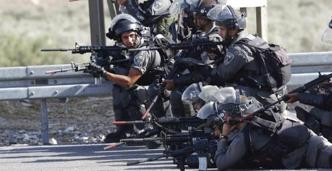 Soldados israelíes toman posiciones frente a manifestantes palestinos durante los enfrentamientos en el puesto de control de Howara, cerca de Nablus, Cisjordania.-  EFE / EPA / ALAA Badarneh