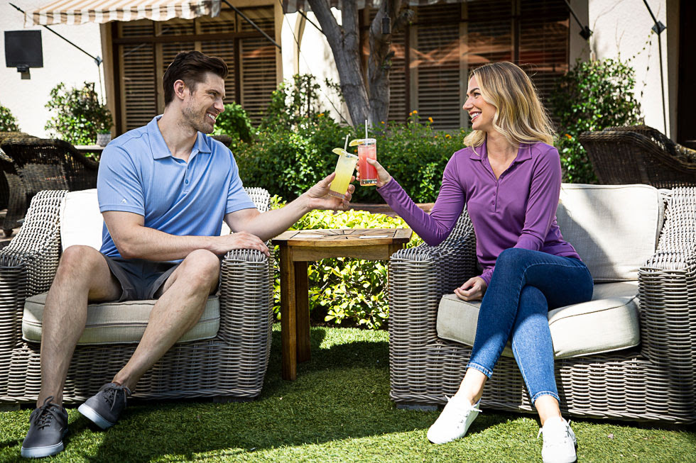 man and woman toasting with cocktails outdoors at The Wigwam Bar