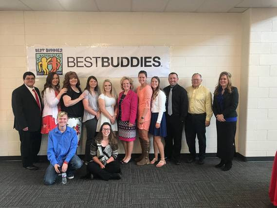 "Superintendent Balow stands with participants and leaders from the Rawlins Best Buddies program underneath a big banner that reads, ""Best Buddies""."