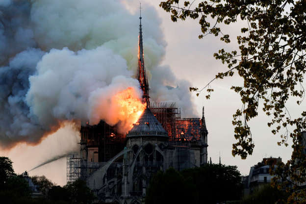 Slide 19 of 31: Flames and smoke are seen billowing from the roof at Notre-Dame Cathedral in Paris on April 15, 2019. - A fire broke out at the landmark Notre-Dame Cathedral in central Paris, potentially involving renovation works being carried out at the site, the fire service said. (Photo by Geoffroy VAN DER HASSELT / AFP)        (Photo credit should read GEOFFROY VAN DER HASSELT/AFP/Getty Images)