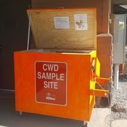 A CWD sampling kiosk, painted orange with its lid open.