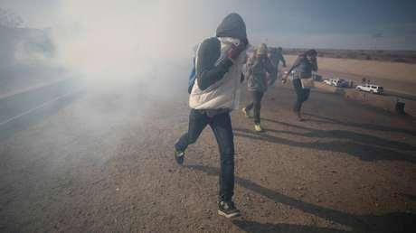 Migrantes huyen del gas lacrimógeno lanzado por los agentes fronterizos estadounidenses cerca de la valla entre México y EE.UU., Tijuana 25 de noviembre de 2018.