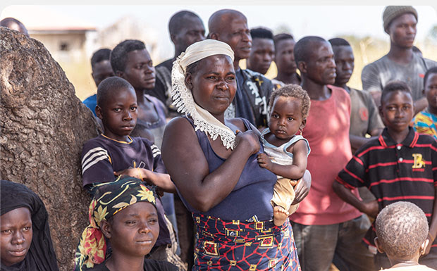 Nigerian people standing; woman holding baby
