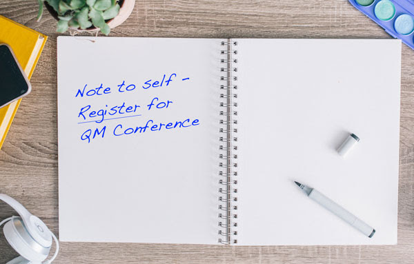 notebook with note to self: register for QM conference written in it