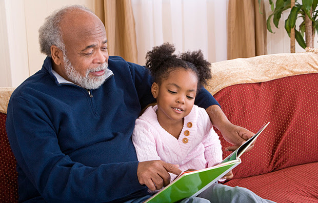 A grandfather reading to his granddaughter.