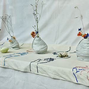A photograph of a window display with bases and flowers.