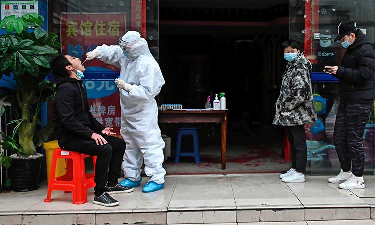 Nhân viên y tế mặc đồ bảo hộ lấy mẫu xét nghiệm nCoV cho dân tại thành phố Vũ Hán, Trung Quốc, ngày 29/3. Ảnh: AFP.