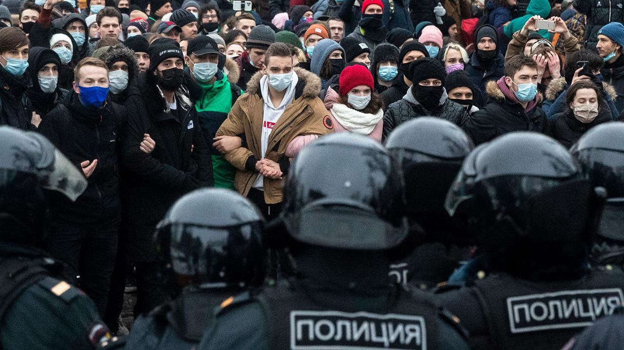 People stand in front of police officers during a protest against the jailing of opposition leader Alexei Navalny in Moscow, Russia, Jan. 23, 2021.