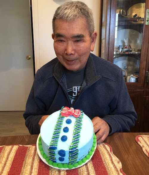 Image of older man with short grey hair and a dark blue jacket in front of a cake that says Dad