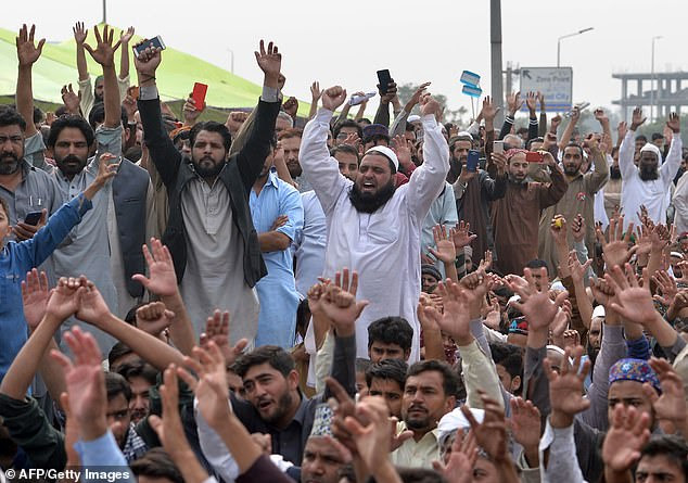 Islamic fundamentalists raise their arms and chant slogans on the Faizabad bridge in Islamabad, blocking the overpass amid fresh protests over Asia Bibi's acquittal