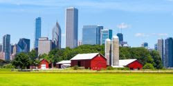 Photo of a farm in the foreground with a city skyline in the background