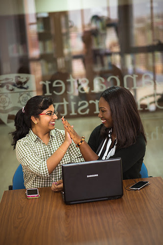 Two female students high-fiving in front of a laptop.