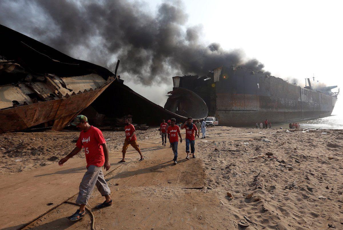 Rescue workers walk near the burning oil tanker at the ship-breaking yard in Gaddani, Pakistan, November 2, 2016. REUTERS/Akhtar Soomro