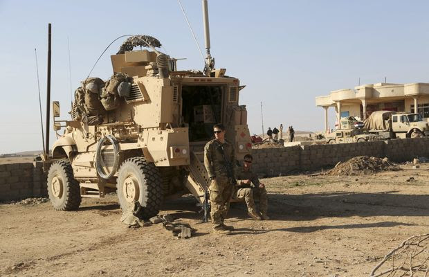 In this Thursday, Feb. 23, 2017, file photo, U.S. Army soldiers stand outside their armored vehicle on a joint base with Iraqi army south of Mosul, Iraq. (AP Photo/ Khalid Mohammed) ** FILE **