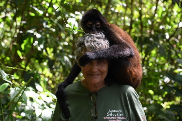 Carol with spider monkey on her shoulders, arm wrapped around Carol's head