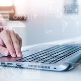 Close up do homem de negócio que datilografa no computador portátil
