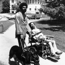 Image is a photo of Black man, Don Galloway, with an Afro and wearing a dashiki holding the harness of a black guide dog. Don is standing next to a white person, Disability Rights leader Ed Roberts, using a power wheelchair with a goatee and long hair. The image is in black and white and is located on the campus of Berkeley in 1974.