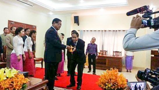 Deputy Prime Minister Sar Kheng (centre left) presents the incoming Stung Treng governor, Mom Saroeun, with an official stamp late last year during a handover ceremony. Photo supplied