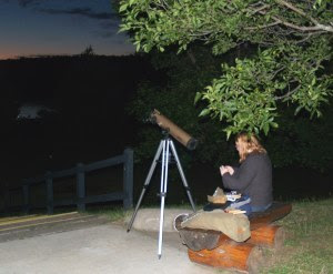 park visitor sits next to telescope near lake