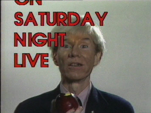 "A video still of a person holding an apple and looking towards the camera. A ""Saturday Night Life"" graphic in red, capital letters appears in the foreground."