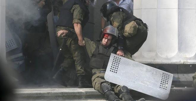 Varios agentes retiran a un compañero herido durante los enfrentamientos en Kiev. - REUTERS