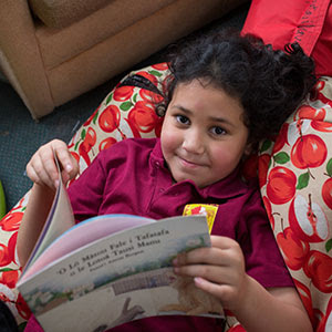 Young Pasifika girl reading a Samoan language book while sitting in a beanbag