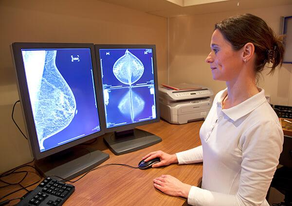 Technician looking at mammogram x-rays