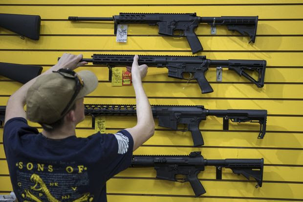 An employee places a rifle back on the wall at ABQ Guns in Albuquerque, N.M., on Saturday. New Mexico is one of the states where the 'Second Amendment sanctuary' movement has taken hold.