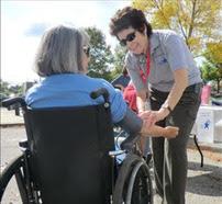MRC volunteer helping someone in a wheelchair