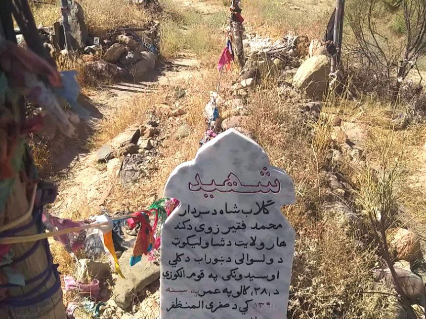 A grave site with a gravestone and colourful decorations.