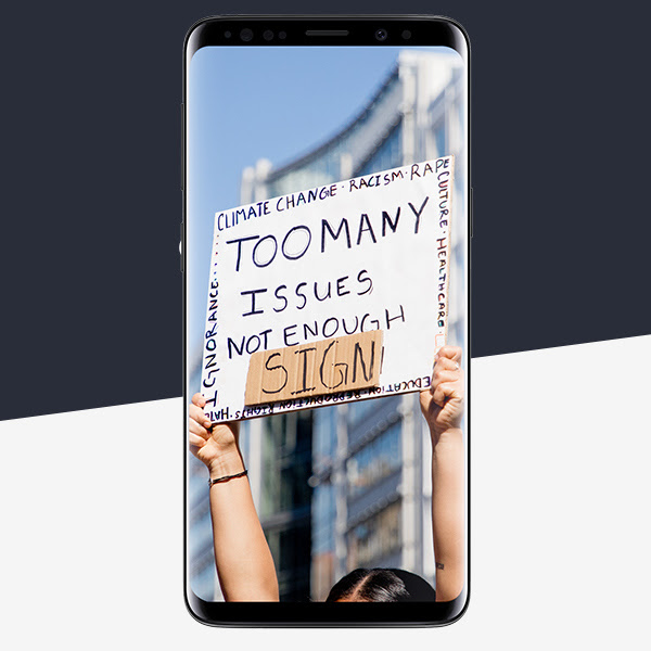 The Samsung S9 showing a woman holding a sign saying 'Too Many Issues Not Enough Sign'