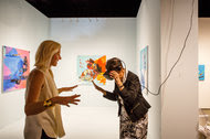 Visitors at the Seattle Art Fair explore an exhibit by Rachel Rossin that includes paintings and virtual reality goggles.