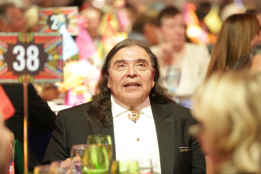 Marshall McKay, his long hair loose around his shoulders, in a formal jacket at a museum event