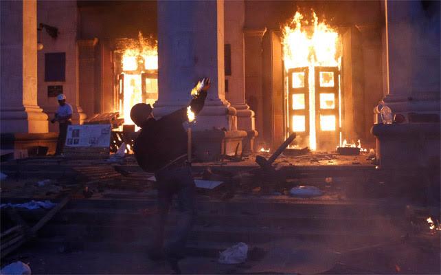 Un manifestante lanza un artefacto incendiario al edificio ya ardiendo.
