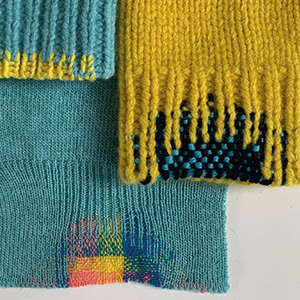 A photograph of three jumpers' cuffs which have been mended in colourful wools.