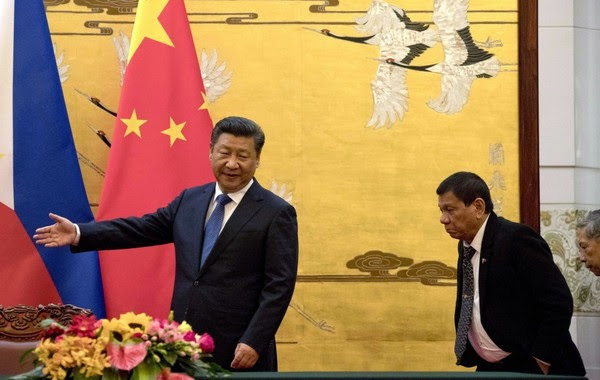 Duterte is shown the way by Chinese President Xi Jinping before a signing ceremony in Beijing in 2016. (Ng Han Guan/Associated Press)