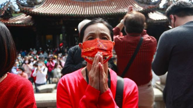 Taiwanese people wearing a face mask pay worships at Lungshan Temple