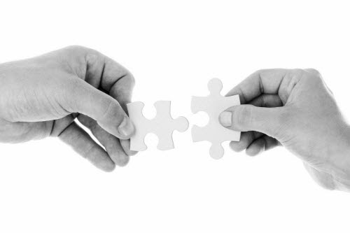 Two adult hands coming together with jigsaw puzzle pieces to link in center.