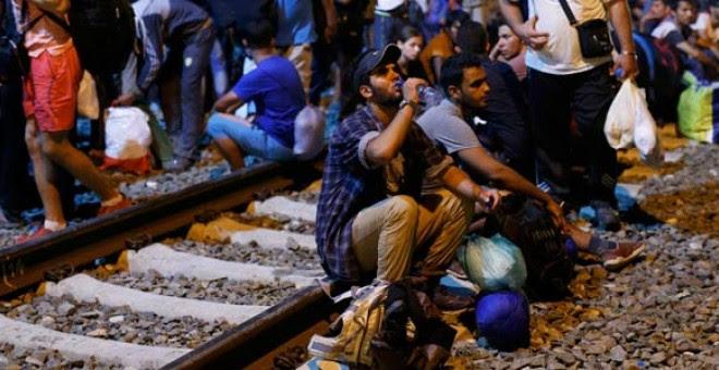 Un grupo de refugiados espera en la estación de la ciudad fronteriz de Tobarnik. / ANTONIO BRONIC (REUTERS)
