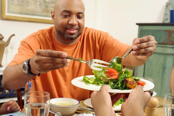A man serving salad.